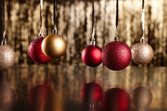 Christmas balls on black background. Red and golden christmas balls on a golden and shiny backround Royalty Free Stock Photo