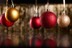 Christmas balls on black background. Red and golden christmas balls on a golden and shiny backround Royalty Free Stock Images