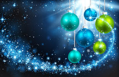 Christmas balls on a blue background. Christmas color balls on a blue background with snowflakes and bright rays of light Royalty Free Stock Images