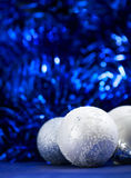 Christmas balls on blue bokeh background. White and silver christmas balls on dark blue bokeh background with space for text. Merry christmas card. Xmas. New Stock Images