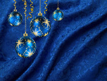 Christmas balls blue curtain. Christmas balls hanging against vivid blue folded damask curtain stock image