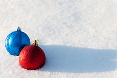 Christmas balls. Blue and red Christmas balls lies on a snow Stock Photos
