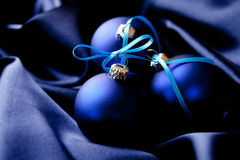 Christmas balls on blue satin Royalty Free Stock Photos