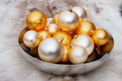 Christmas balls in bowl. Christmas balls in mirror bowl on reindeer fur coat royalty free stock photo
