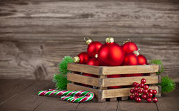 Christmas balls in box with fir on wooden board Stock Photos