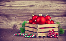 Christmas balls in box with fir on wooden board Royalty Free Stock Image