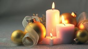 Christmas Balls and Candles are Burning. Christmas still life. Golden balls, ribbons and burning candles stock video footage