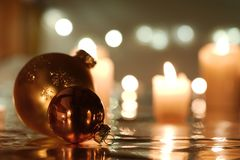 Christmas balls with candles. Golden Christmas balls against candlelight background Royalty Free Stock Photography