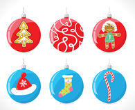 Christmas balls on the Christmas tree of red and blue color with a pattern sock, hats, candy, strips and sand girl Stock Photos