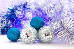 Christmas balls with colored lights. Christmas balls with silver garland lit with colored lights royalty free stock photos