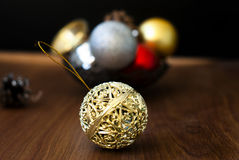 Christmas balls and cones on a wooden background. Openwork gold Christmas ball closeup and other New Year's toys on the wooden background with bright bokeh in Stock Images