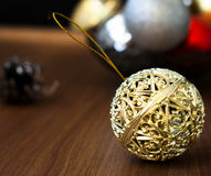 Christmas balls and cones on a wooden background. Openwork gold Christmas ball closeup and other New Year's toys on the wooden background with bright bokeh in Royalty Free Stock Photos