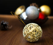 Christmas balls and cones on a wooden background. Openwork gold Christmas ball closeup and other New Year's toys on the wooden background with bright bokeh in Royalty Free Stock Photography
