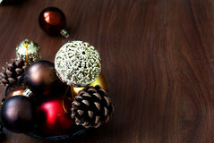 Christmas balls and cones on a wooden background. Openwork gold Christmas ball closeup and other New Year's toys on the wooden background with bright bokeh in Royalty Free Stock Photo