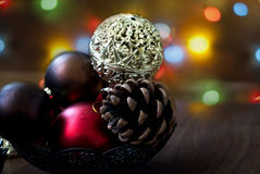 Christmas balls and cones on a wooden background. Openwork gold Christmas ball closeup and other New Year's toys on the wooden background with bright bokeh in Stock Photos