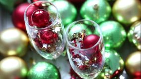 Christmas balls and confetti in wineglass on a bright abstract background stock footage