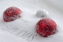 Christmas balls covered with snow. Red christmas balls covered with snow and caption Stock Photo