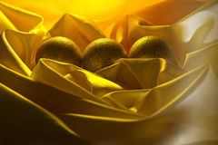 Christmas balls decoration on a yellow satin cloth Royalty Free Stock Image