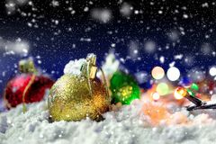 Christmas balls. Christmas decorative balls on the snow under snowfall royalty free stock photo