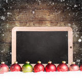 Christmas balls with empty chalkboard in the snow Royalty Free Stock Image