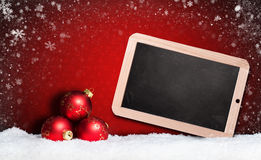 Christmas balls with empty chalkboard in the snow Royalty Free Stock Photos