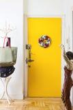Christmas balls felt crown. On yellow door Royalty Free Stock Photos