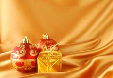 Christmas balls and gift. Two christmas balls and gift on the gold bacground Stock Photography