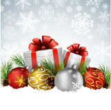 Christmas balls with gift, fir and pine cone on the snow Royalty Free Stock Images