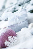 Christmas balls and gift in snow. Beautiful christmas tree balls in snow together with a gift and some ornaments Royalty Free Stock Photos