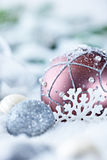 Christmas balls and gift in snow. Beautiful christmas tree balls in snow together with a gift and some ornaments Stock Photo