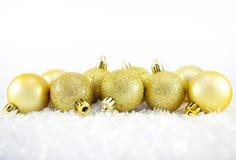 Christmas balls. Gold christmas balls with snow Royalty Free Stock Photo