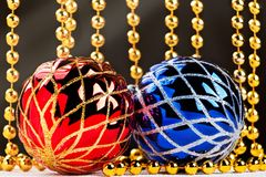 Christmas balls and golden garland with light beams on dark background. Stock Images