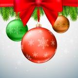 Christmas balls, green fir branches, bow, snowflake background. Gold Christmas balls with green fir branches on the background made of snowflake. Realistic Stock Image