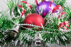 Christmas balls with green garland and silver bells Royalty Free Stock Photography