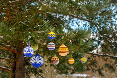 Christmas balls hanging on pine branches covered with snow Stock Photos