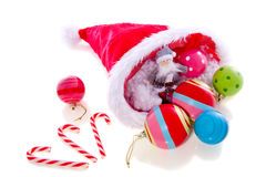 Christmas balls in  hat. Christmas balls in the hat of santaclaus with candycane isolated over white Royalty Free Stock Photo