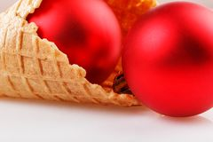 Christmas balls lie in a waffle cup for ice cream on a white background royalty free stock image