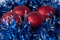Christmas balls are lying in a blue tinsel. Stock Photography