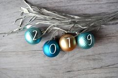 Christmas balls made of gold, turquoise and blue on a wooden background, decorated with a silver thread. I royalty free stock image