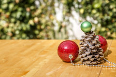 Christmas balls next to pinecone on wooden table, with a background Stock Photography