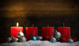 Christmas balls and one of four lit candles Royalty Free Stock Images