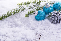 3 christmas balls, pine cones and green branch on snow Stock Photography