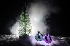 Christmas balls with pine at snow on dark background. Celebration object with free space for text. Selective focus Stock Images