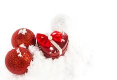 Christmas balls and present. Christmas ball and present in a snow background Royalty Free Stock Images