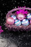 Christmas balls in purple basket on black background with snow. Decorative snowflakes. Royalty Free Stock Image