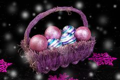 Christmas balls in purple basket on black background with snow. Decorative snowflakes. Stock Photo