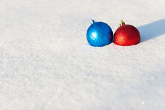 Christmas balls. Red and blue Christmas balls lies in a snow Royalty Free Stock Photos