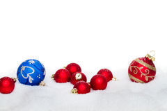 Christmas balls. Red and blue christmas balls in snow - isolated royalty free stock photos