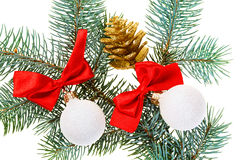 Christmas balls, red bows and cone on fir Stock Photography