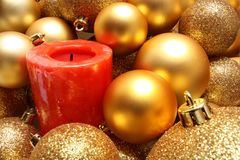 Christmas balls and a red candle Stock Photos